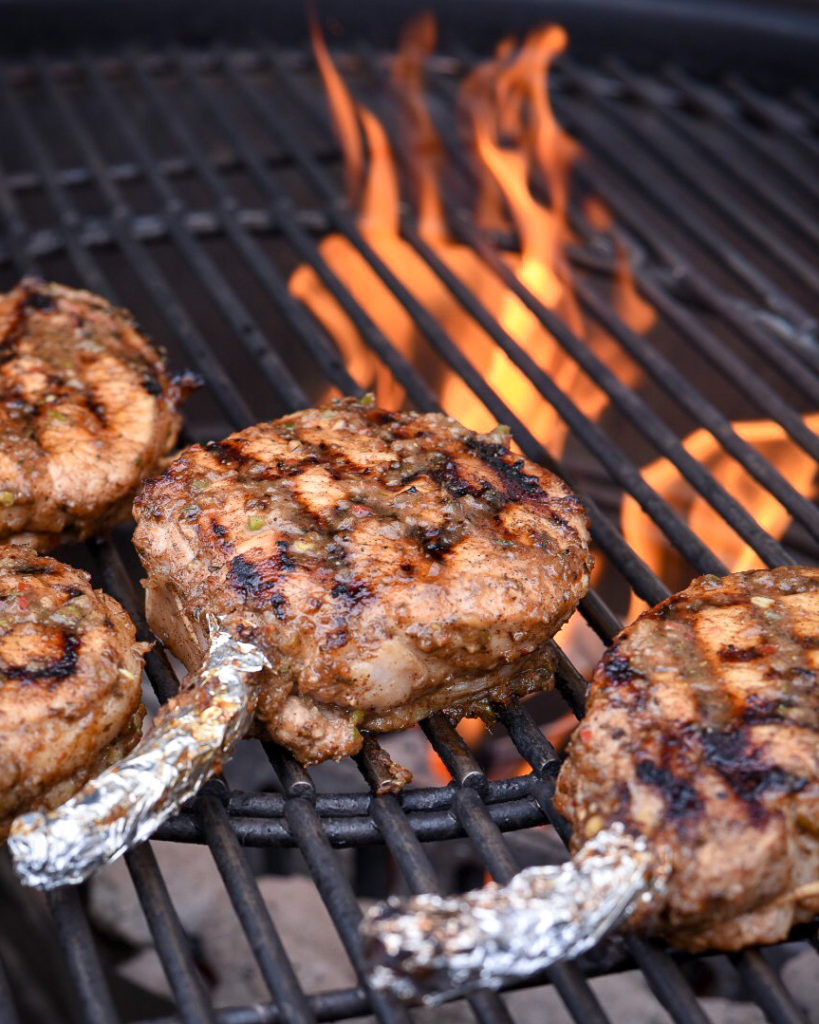 Pork chops on a flaming grill. Frenched bones are covered with aluminum foil.