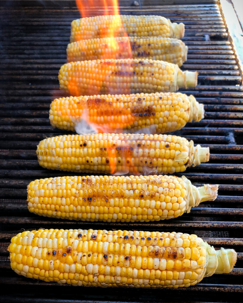 A row of seven nicely charred cobs of corn on a flaming grill.