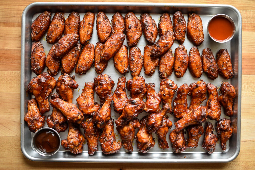 A sheet pan filled lined with chicken wings and two dips.