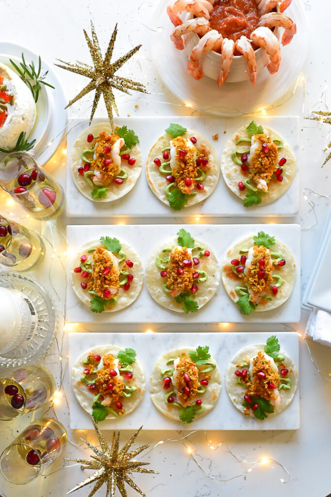 A festive table setting with nine shrimp tortilla bites appetizers and a bowl of shrimp cocktail.