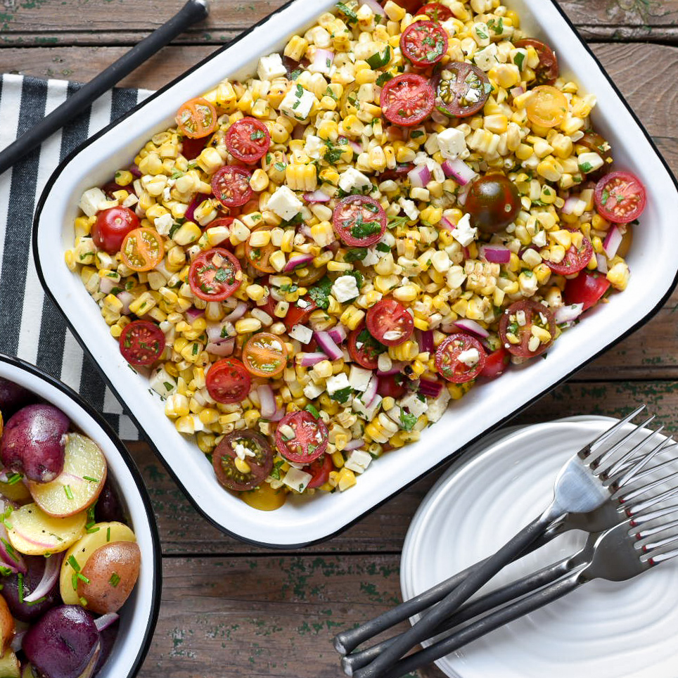 Rectangular white enamel tray with a corn, tomato feta and onion salad. Forks and plates are ready for serving.