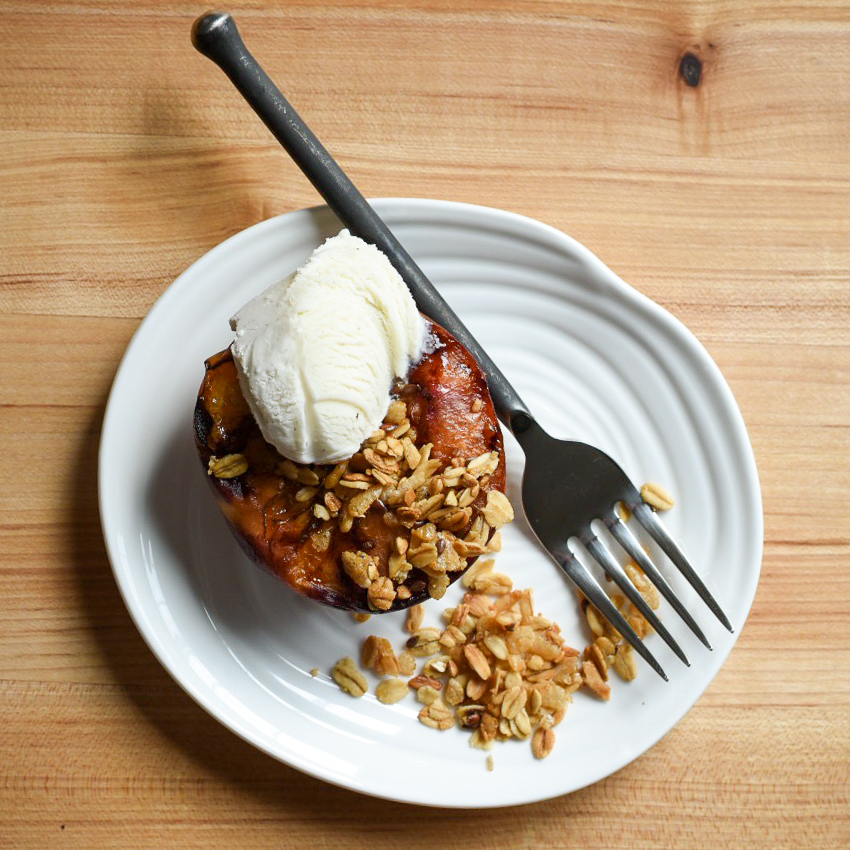 Grilled peach with a crumble topping and a scoop of icecream on a white plate with a black fork.