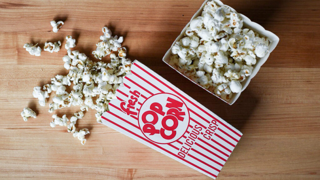 Two popcorn containers: one top down, and one is on it side with popcorn falling out.