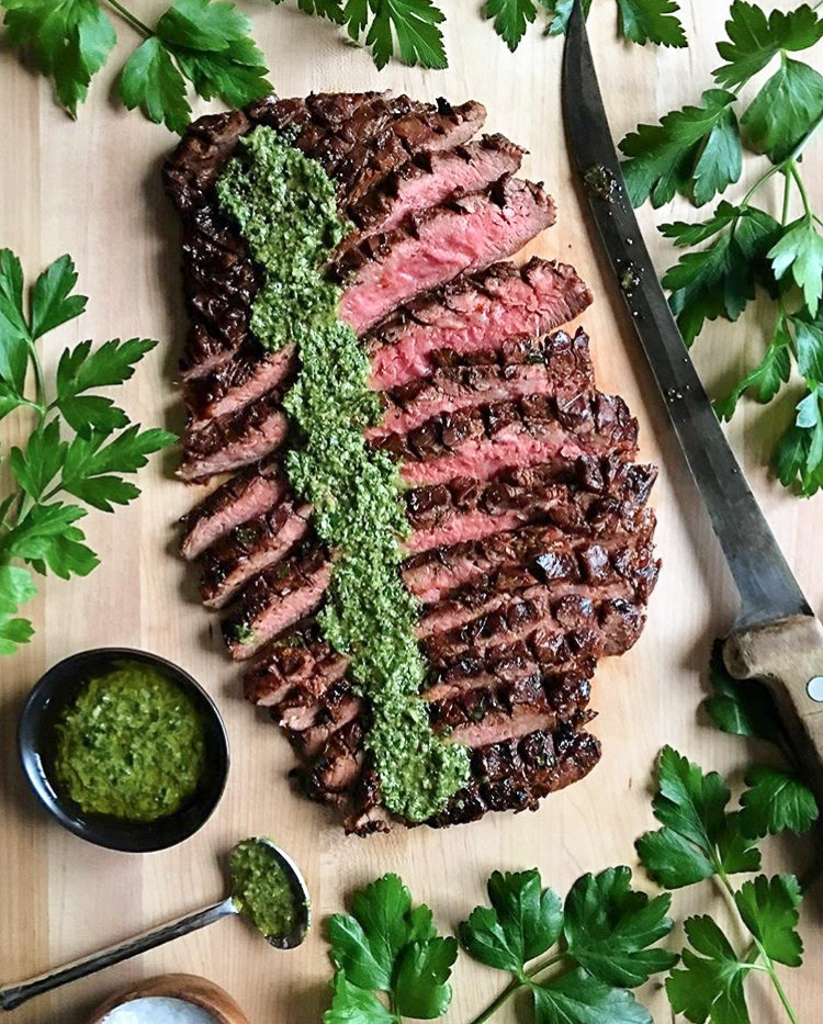 A sliced flank steak with a strip of chimichurri sauce down the top. Surrounded by parsley and a large knife.