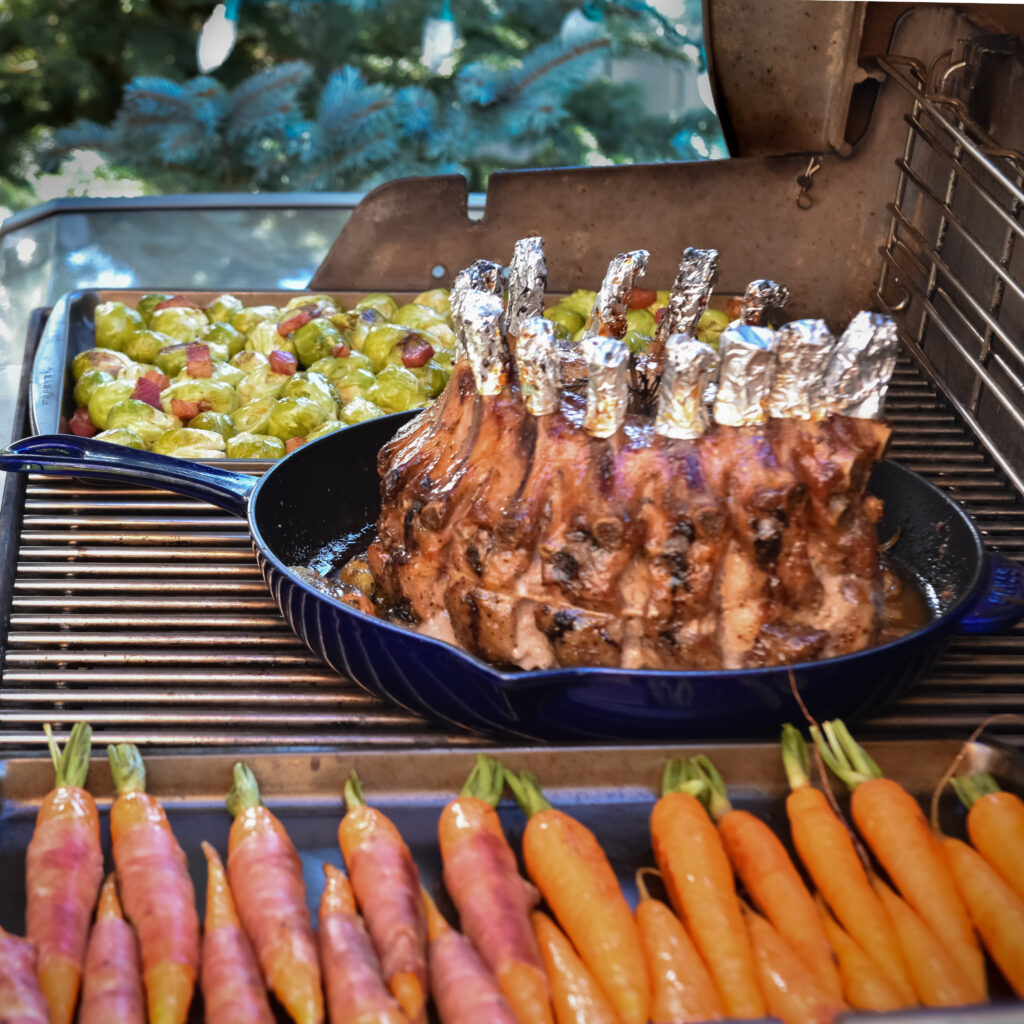 Raw crown roast of pork in a blue cast-iron pan with tin foil on the bones on the barbeque. Carrots and brussels sprouts also on the grill.