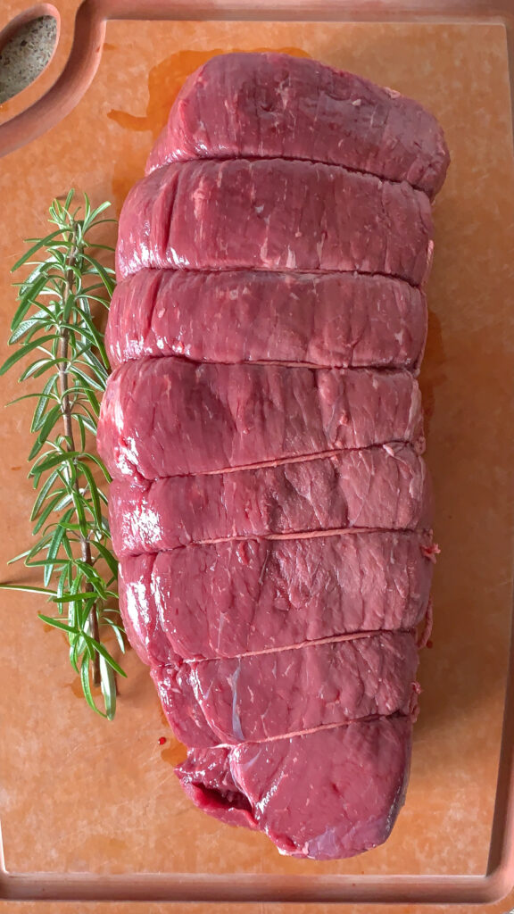 Raw beef roast tied with string on a cutting board with a sprig of rosemary.