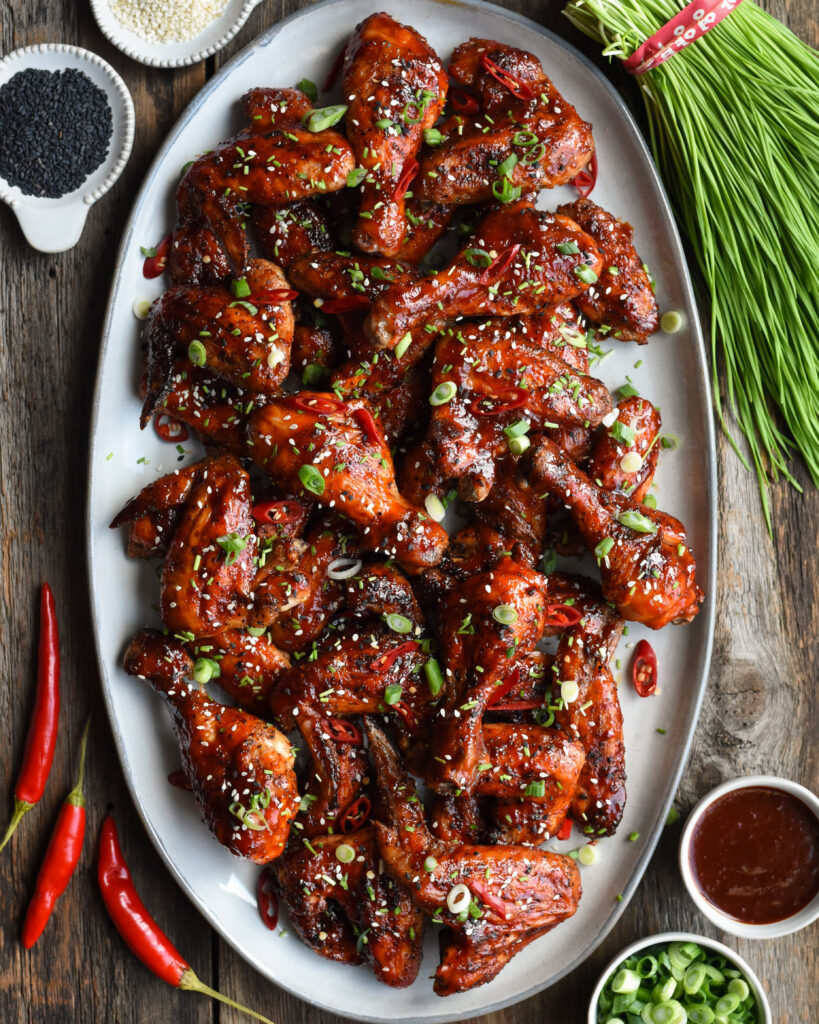 Oval platter of grilled chicken wings with Korean bbq sauce. Red chili peppers, sesame seads and koren chives surrounding the plate.