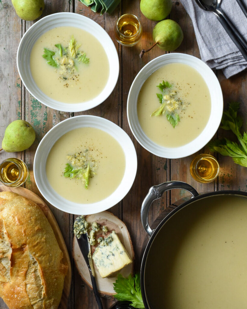 A large pot of  Pear, Port, Potato & Stilton soup with three bowls filled with garnishes. Three glasses of port, pears, cheese and bread are also on the table