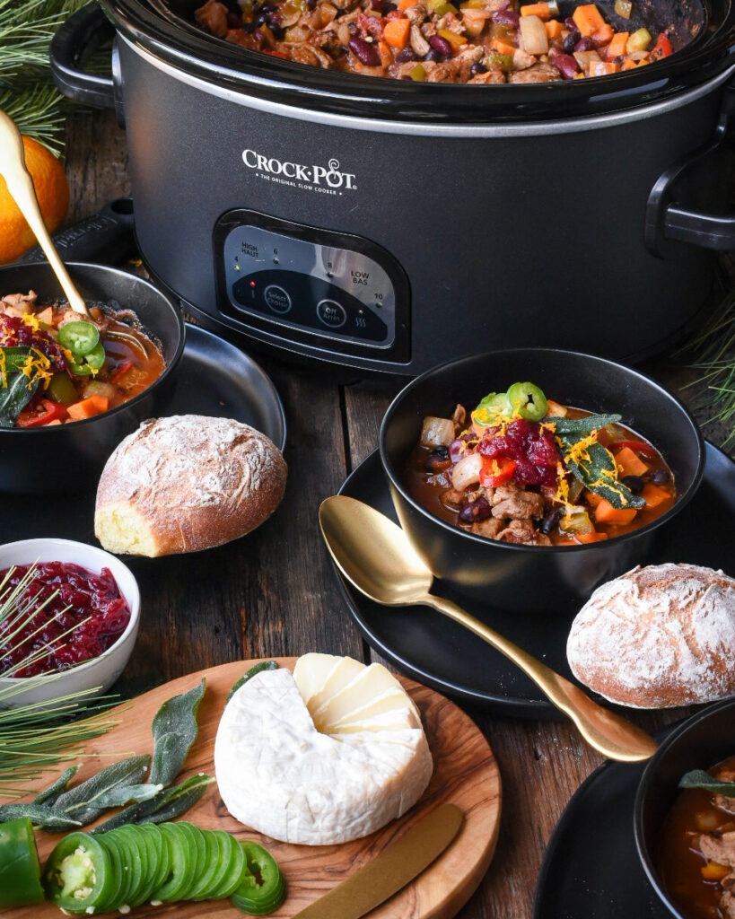 Image of a table with a crock-pot of turkey chili plus two bowls full of chili with bread. The table is decorated with Christmas evergreens and ornaments.