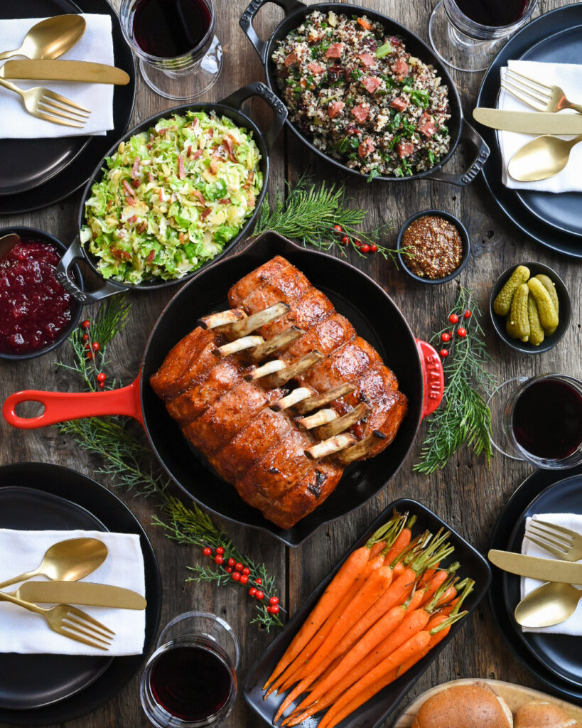 Top down shot of a diner table with two racks of pork in a red skillet pan.  Plus a dish of carrots, quinoa salad, and brussels sprouts. Red wine glasses, pickles, grainy mustard and dinner plates and cutlery.