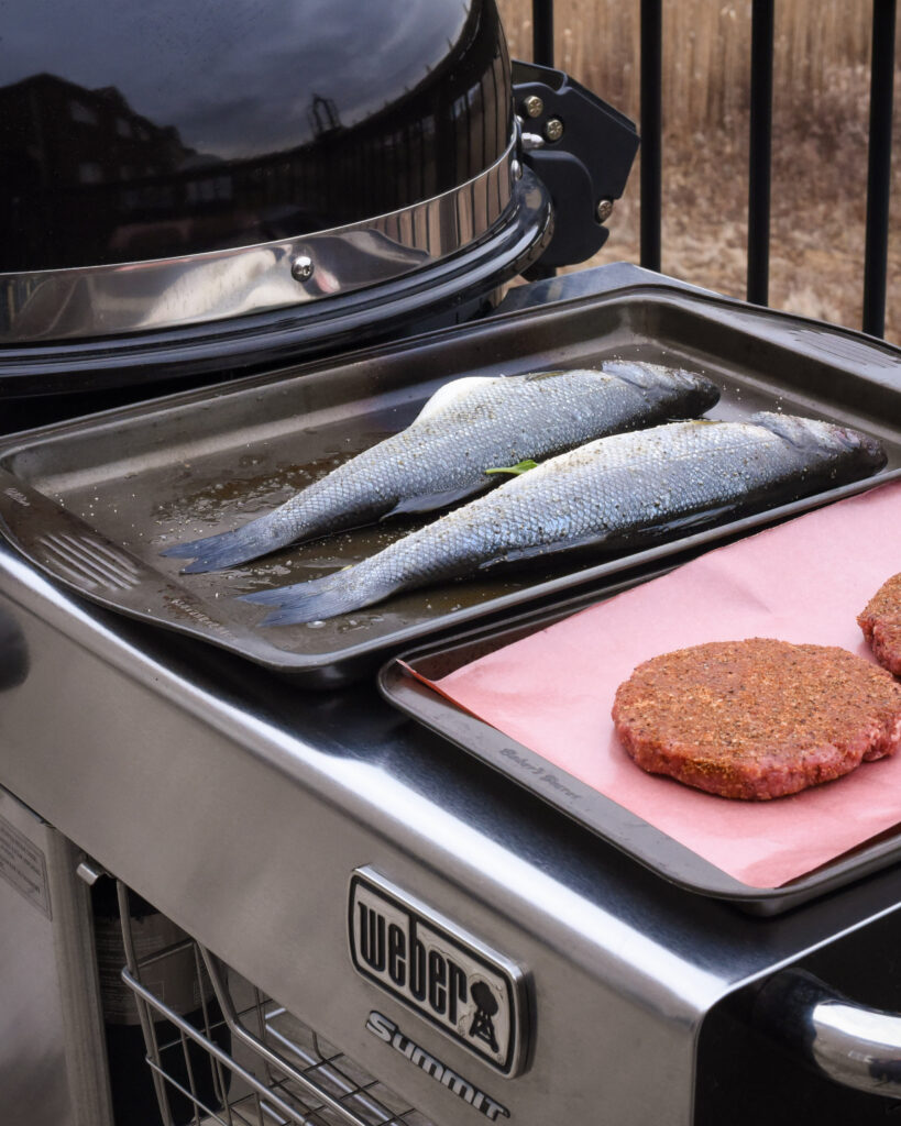 Weber summit charcoal grill with fish and burger patties