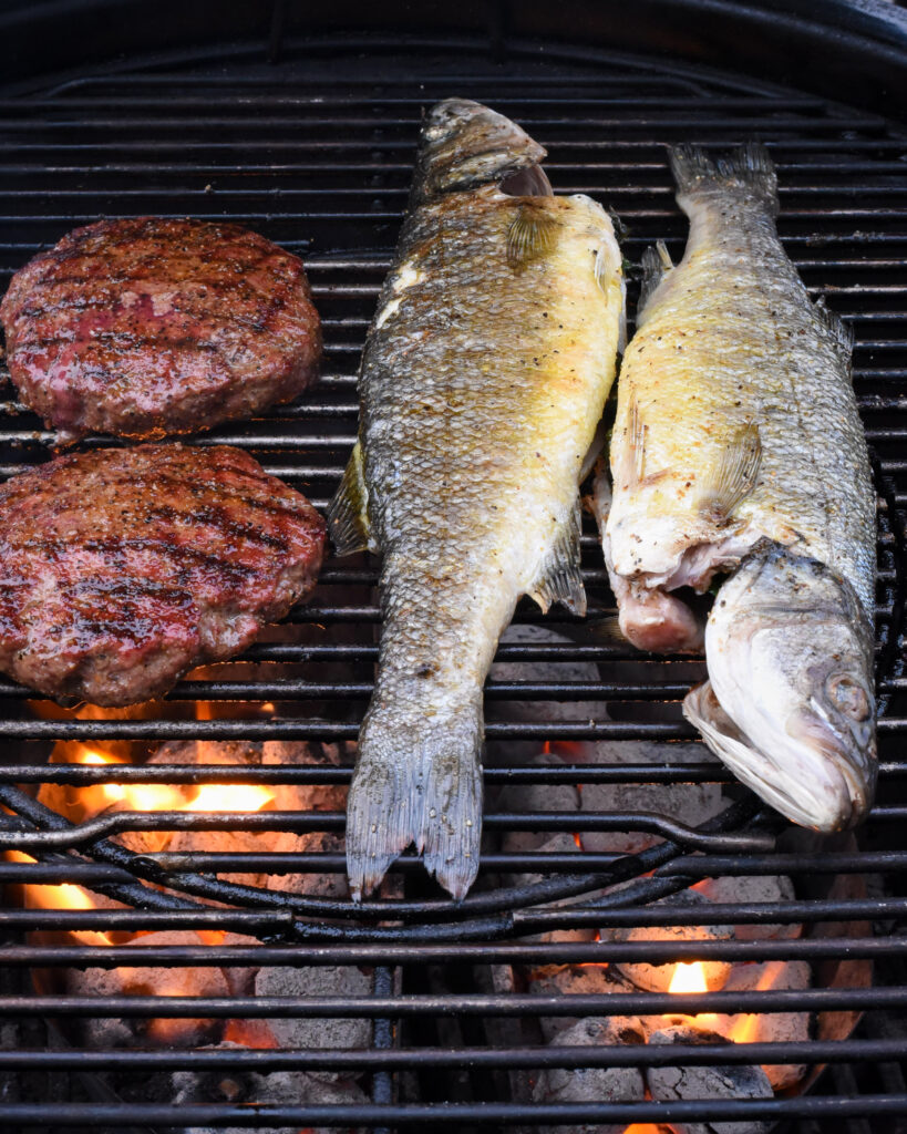 Burgers and fish on a charcoal bbq grill.