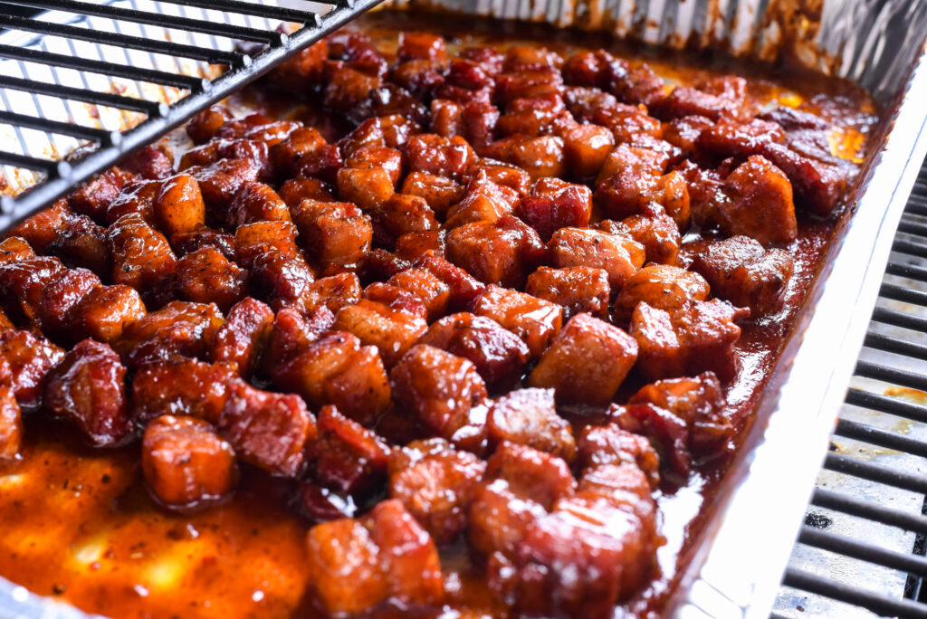 Pork cubes in aluminum pan with sauce in a smoker grill.