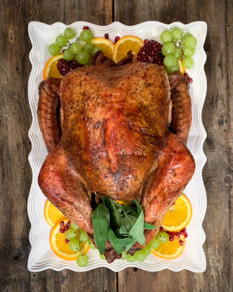 Roasted Turkey on a rectangular platter. Garnished with grapes, oranges and pomegranites.