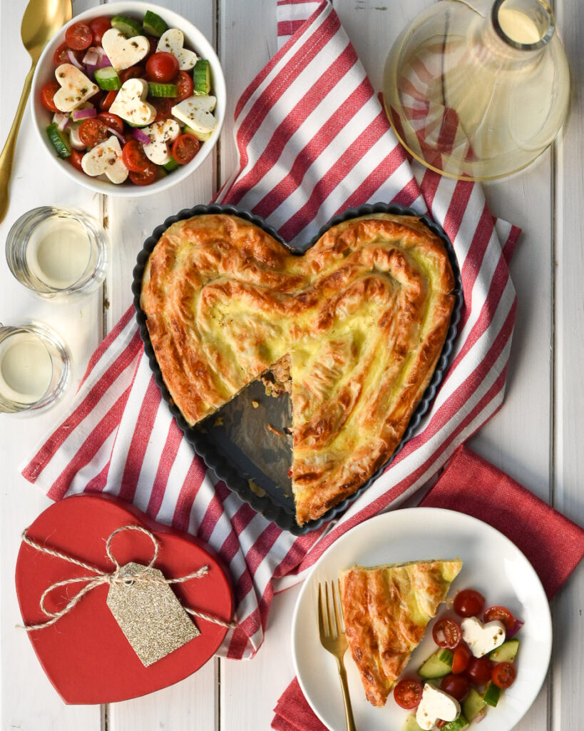Heart shaped phyllo pie with a slice removed. Red and white dishcloth with a tomato and heart shaped feta salad. Two glasses of white wine, a red heart gift box and a plate with a slice of the pie with a gold fork and red napkin.