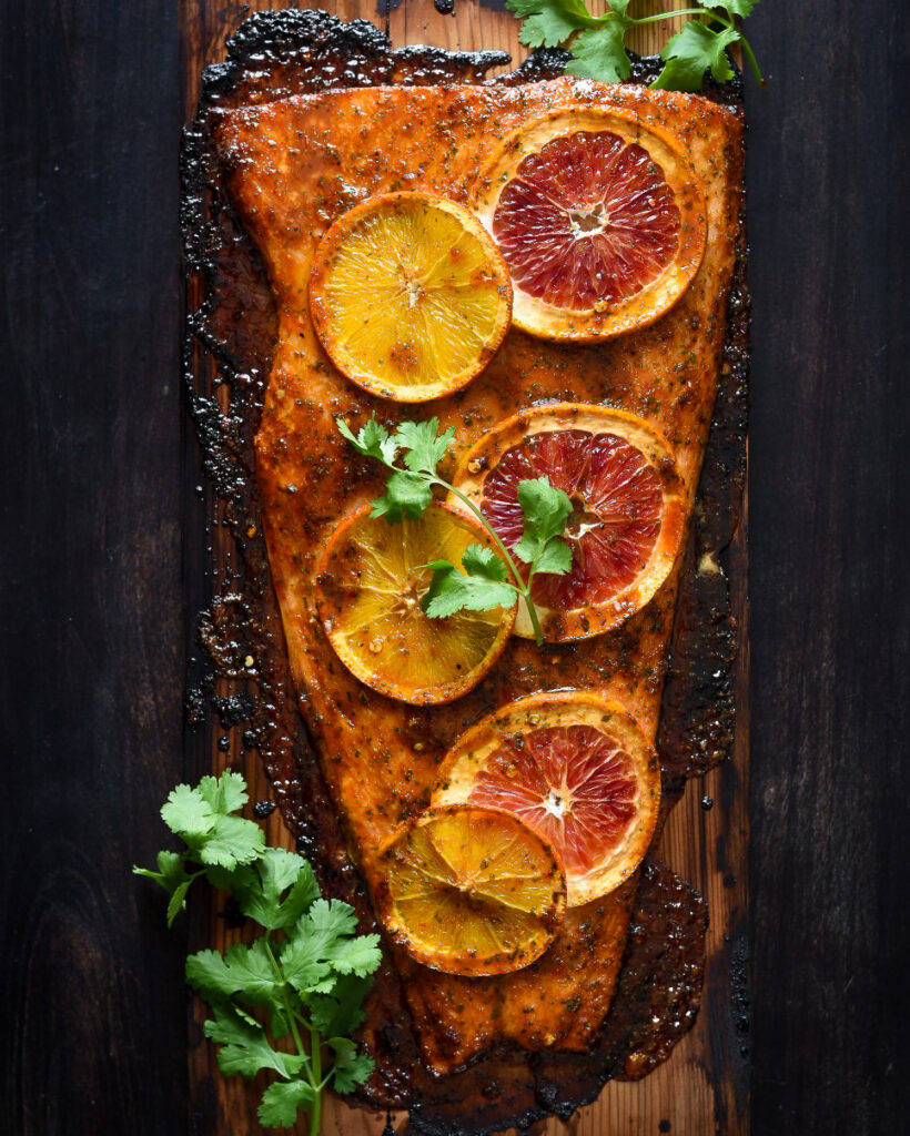 Cedar planked salmon with orange slices and cilantro.