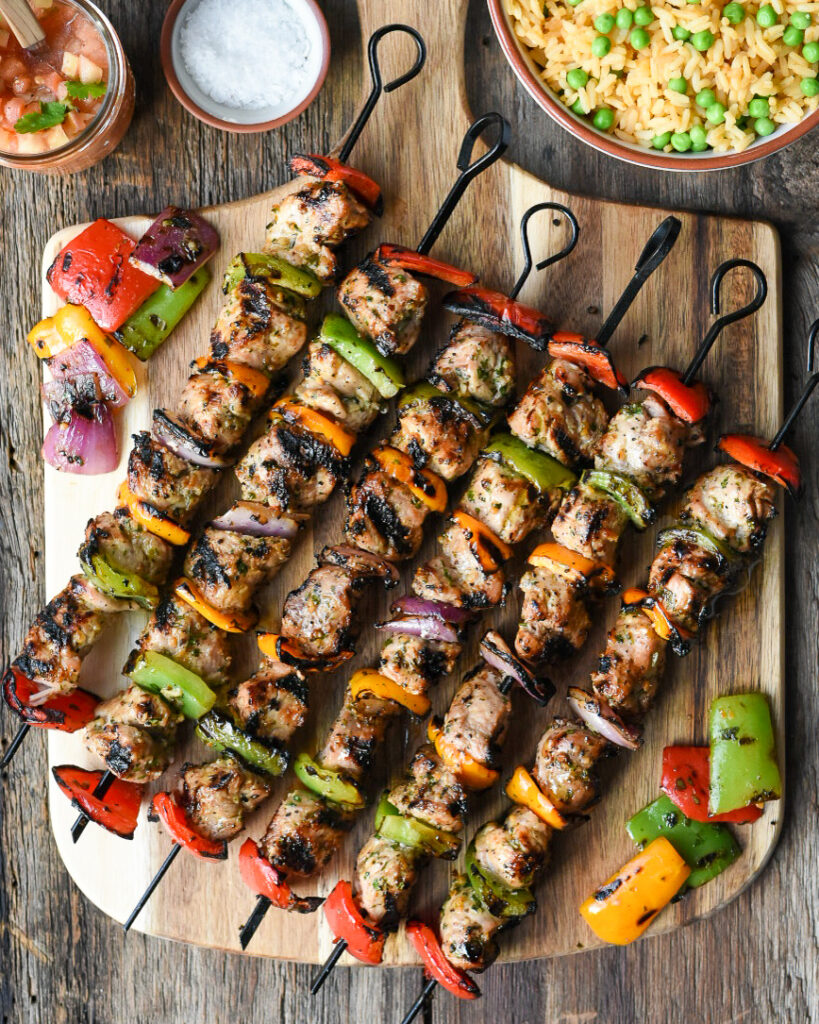 Six colourful, grilled pork tenderloin skewers with veggies on wooden board. Served with rice and peas and salsa.