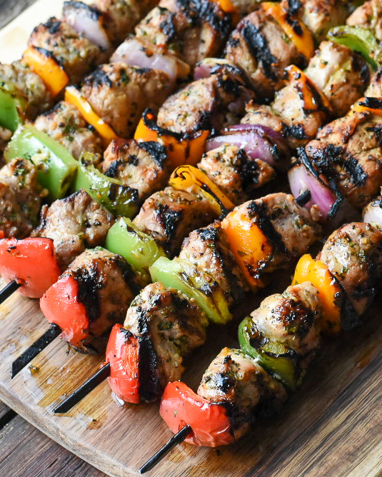 Close-up image of colourful, grilled pork tenderloin skewers.