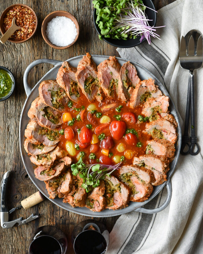 Round platter with a slices of stuffed pork tenderloin with a tomato base in the center.