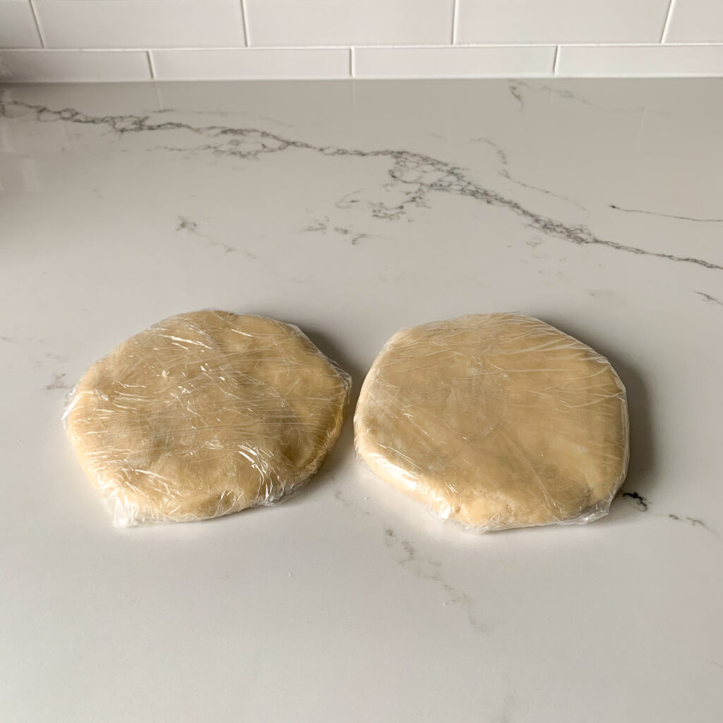 Two rounds of dough wrapped in plastic wrap.