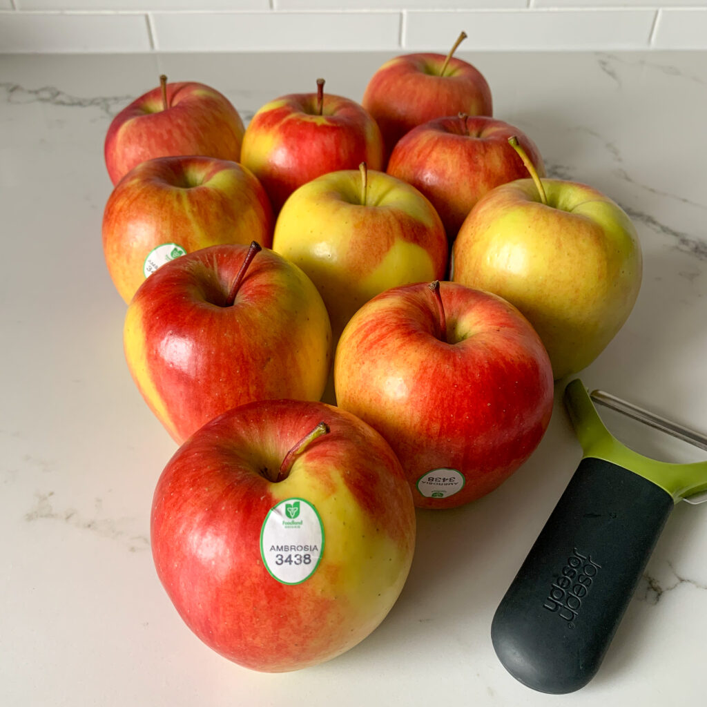 Ten Ambrosia apples with a peeler on the counter. Foodland Ontario tag is on the Ambrosia apple.