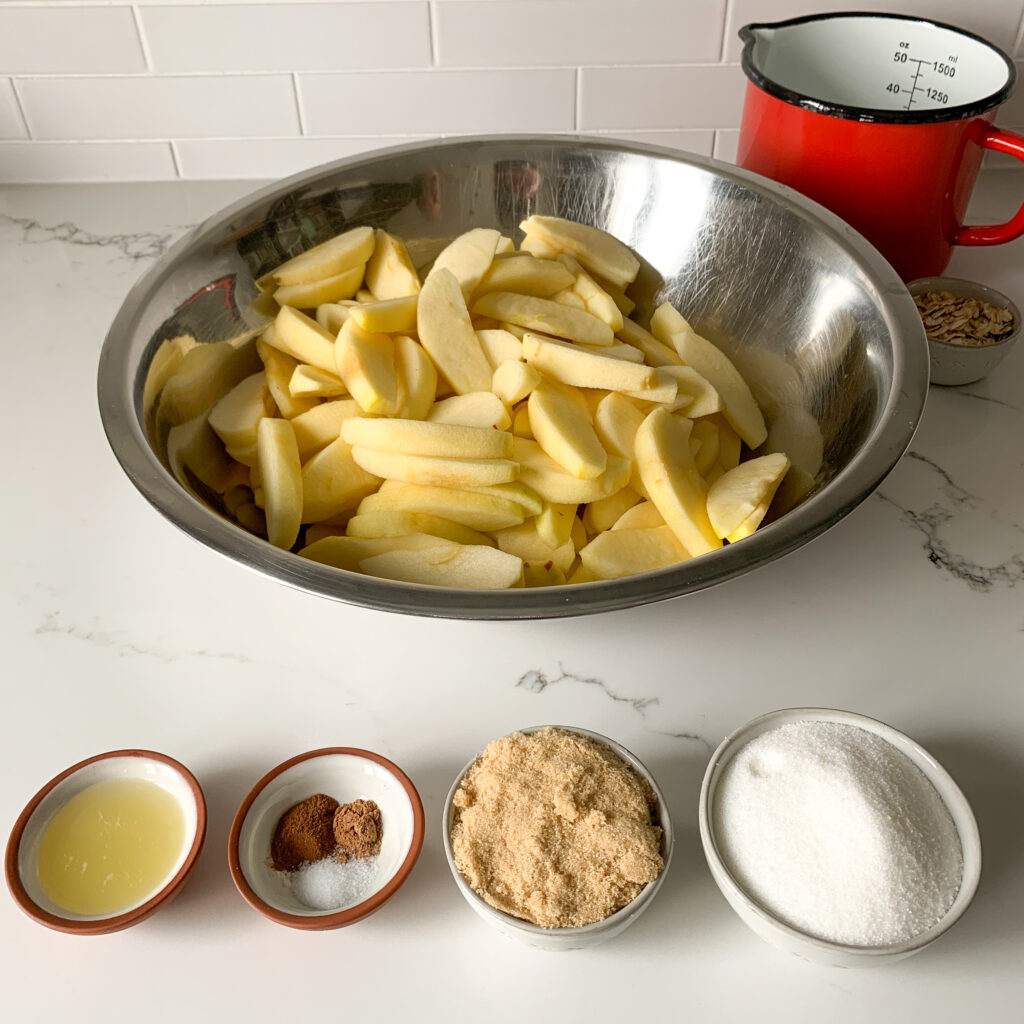 Large stainless steal bowl with sliced apples and four bowls of pie filling ingredients.