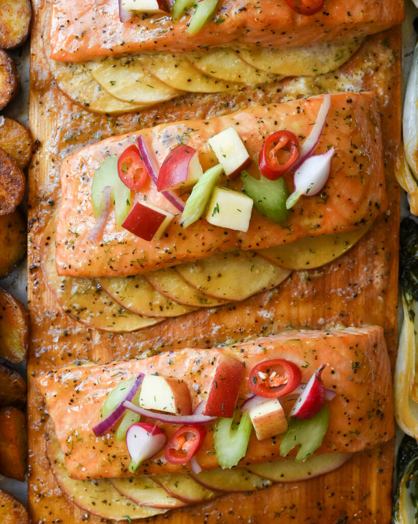 Close up image of the cedar planked salmon. Each piece of salmon is placed on apple slices and topped with an apple salad.