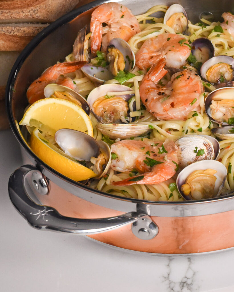 Linguine with clams and shrimps in a copper sauteuse pan with a handle.