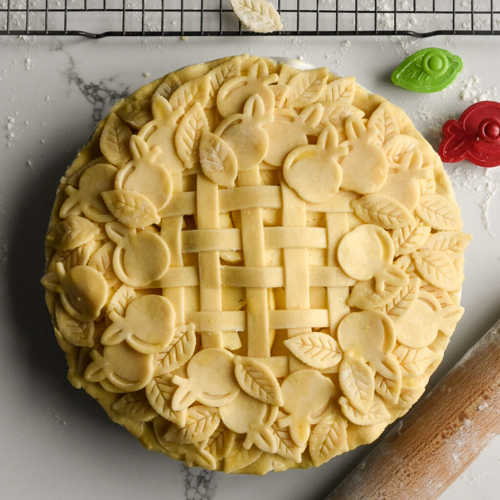 An unbaked pie with a lattice and apple and leaf cut out design.