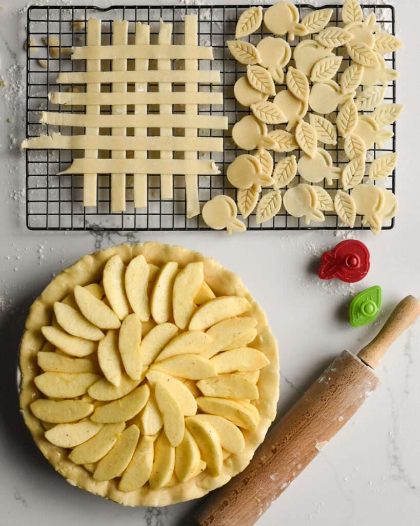 A wire rack with strips and cut outs (apple and leaf shaped) of pie pastry.  A pie filled with apple slices ready for the strips and cut outs to get place on top. A rolling pin and a red and green cut out is beside the pie.