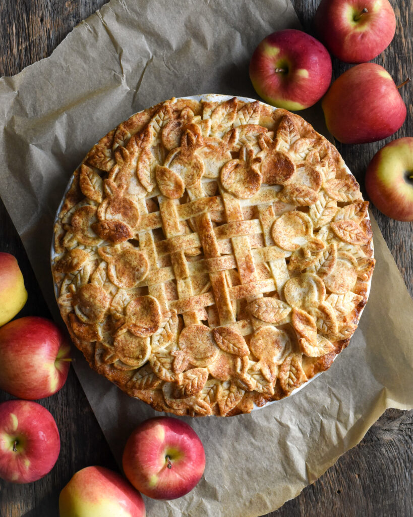 A baked pie with a lattice, apple and leaf cut out design. Apples also surround the pie.
