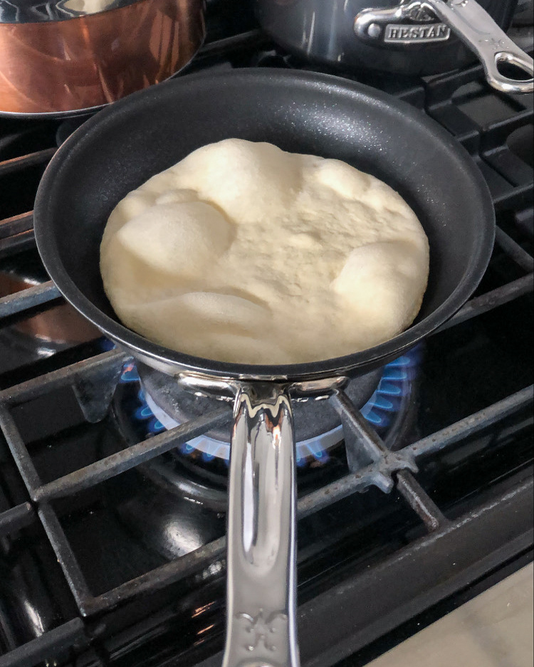A flatbread (naan) being made in a skillet on the stove top.