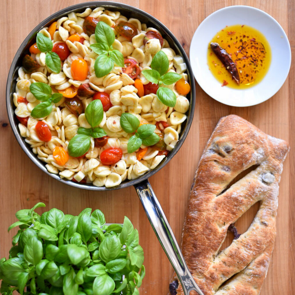 A large pan of Orecchiette with Heirloom Tomatoes, Mozzarella and basil. Surrounded by a dish of chili oil, a basil plant and an olive loaf.
