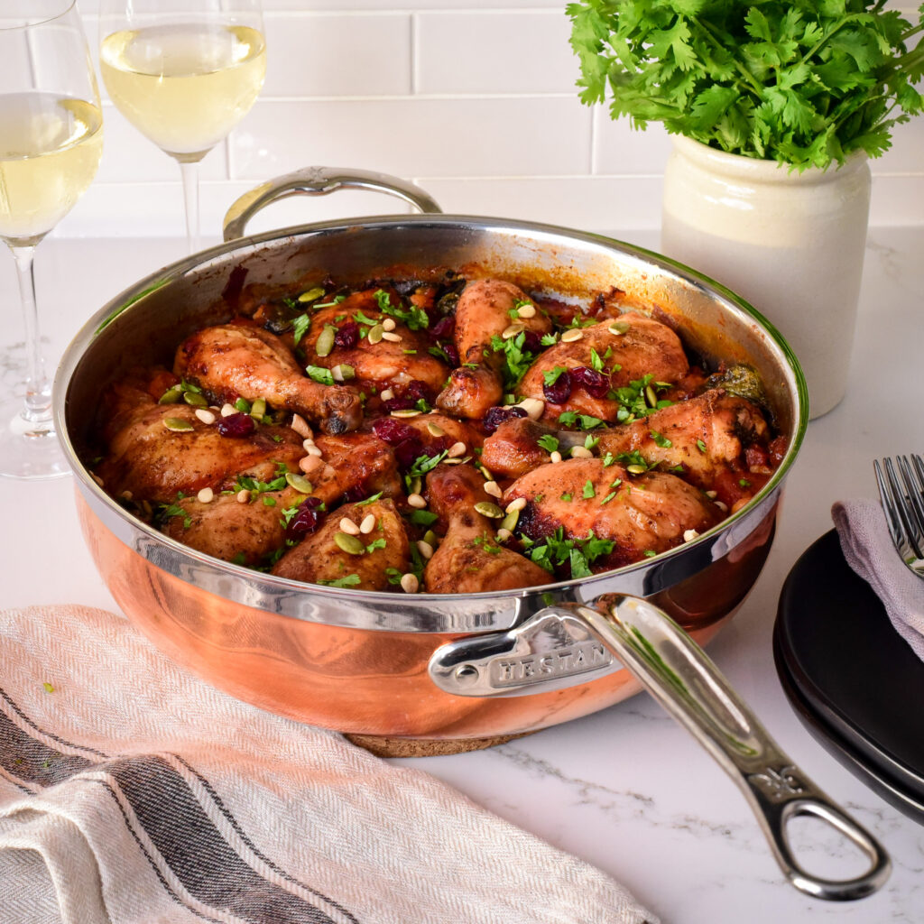 An image of a Moroccan inspired chicken and rice dish in a large copper pan.