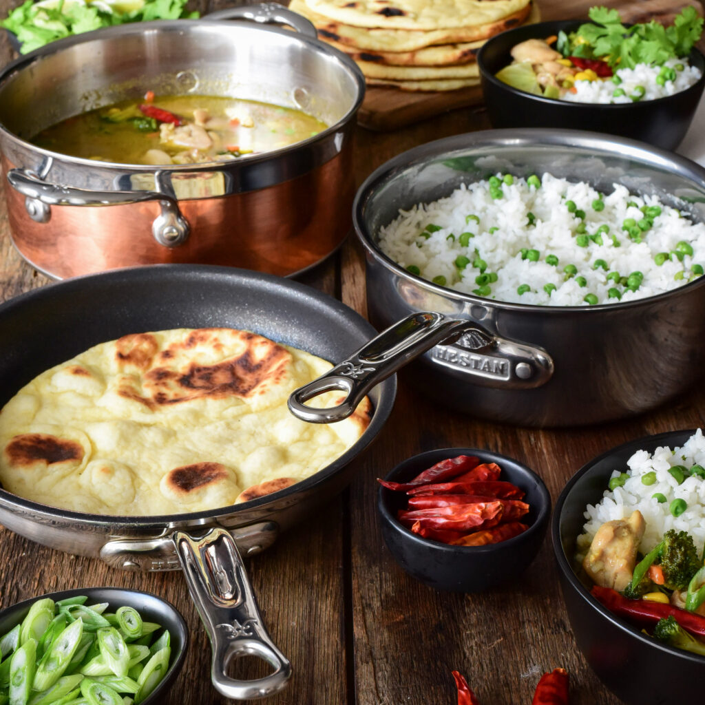 An image of a pot of Thai green curry chicken, a pot of rice and peas, a pan with flatbread (naan) and two bowls with a mixture of everthing.