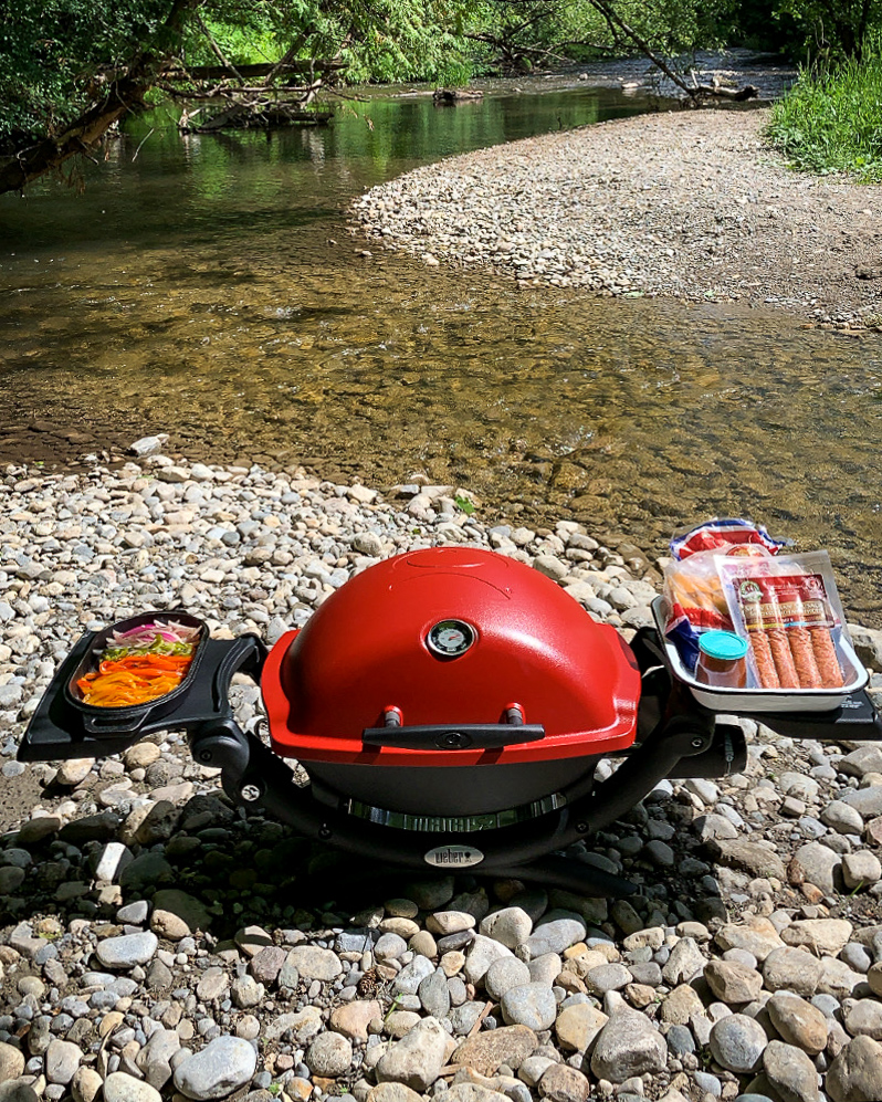 Red bbq with side arms out holding ingredients, by a river.