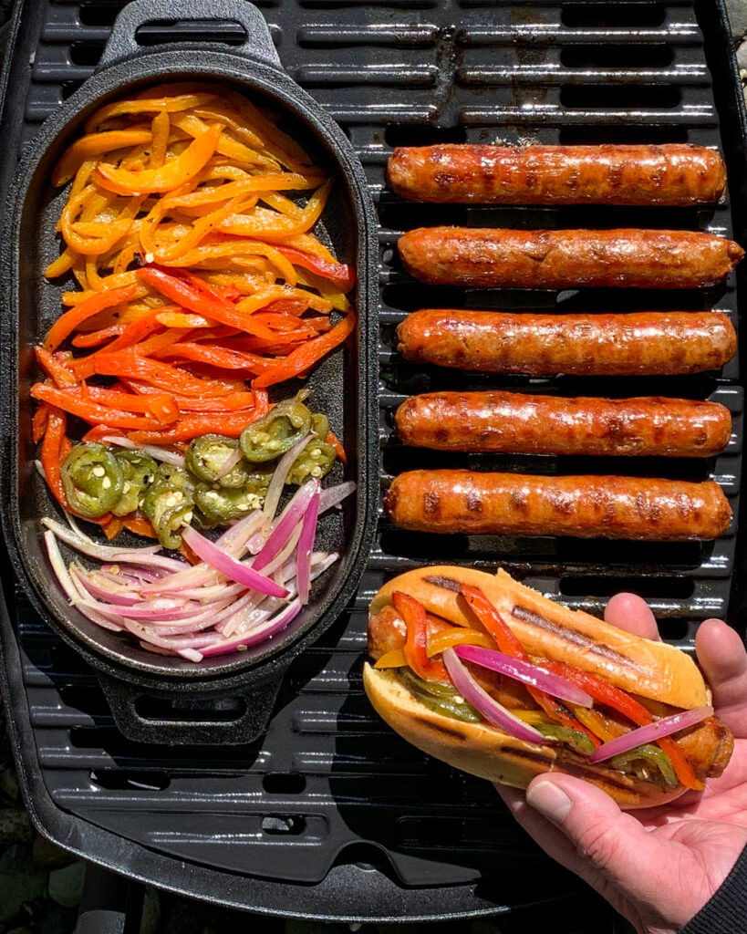 Grilled sausages, peppers and onions on a bbq.