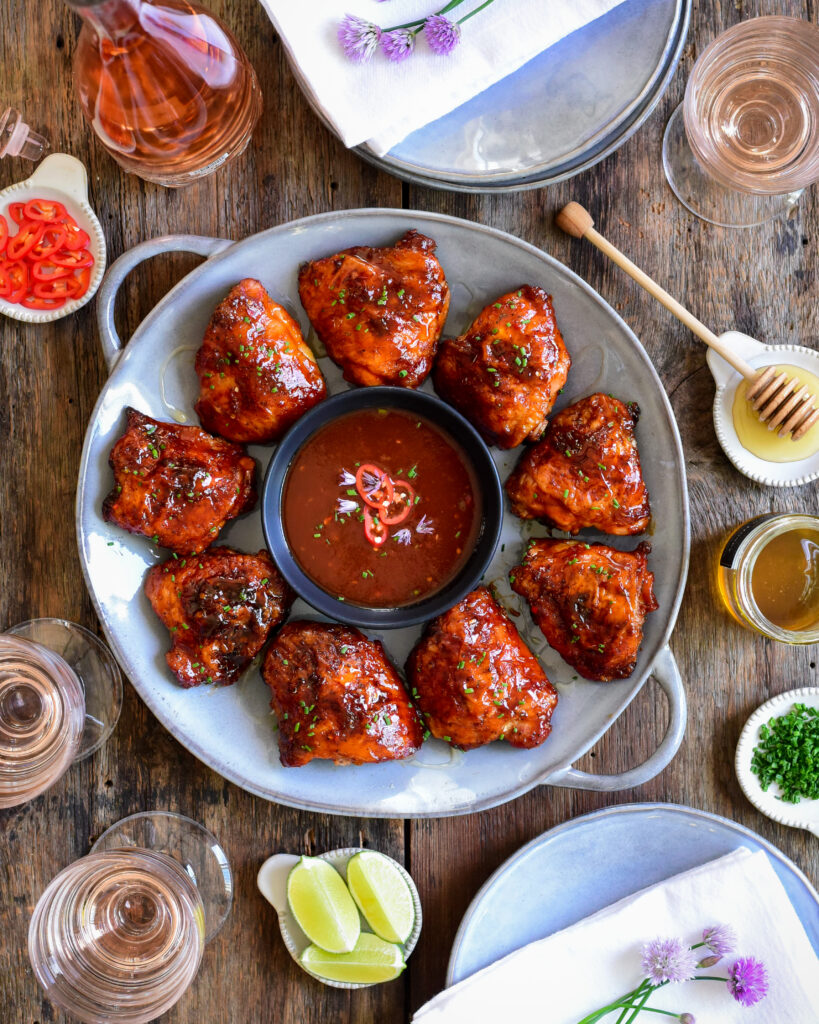 A top down view of a round platter of grilled chicken thighs with a bowl of bbq sauce in the centre. This platter is surrounded by wine glasses, plates, honey and limes.