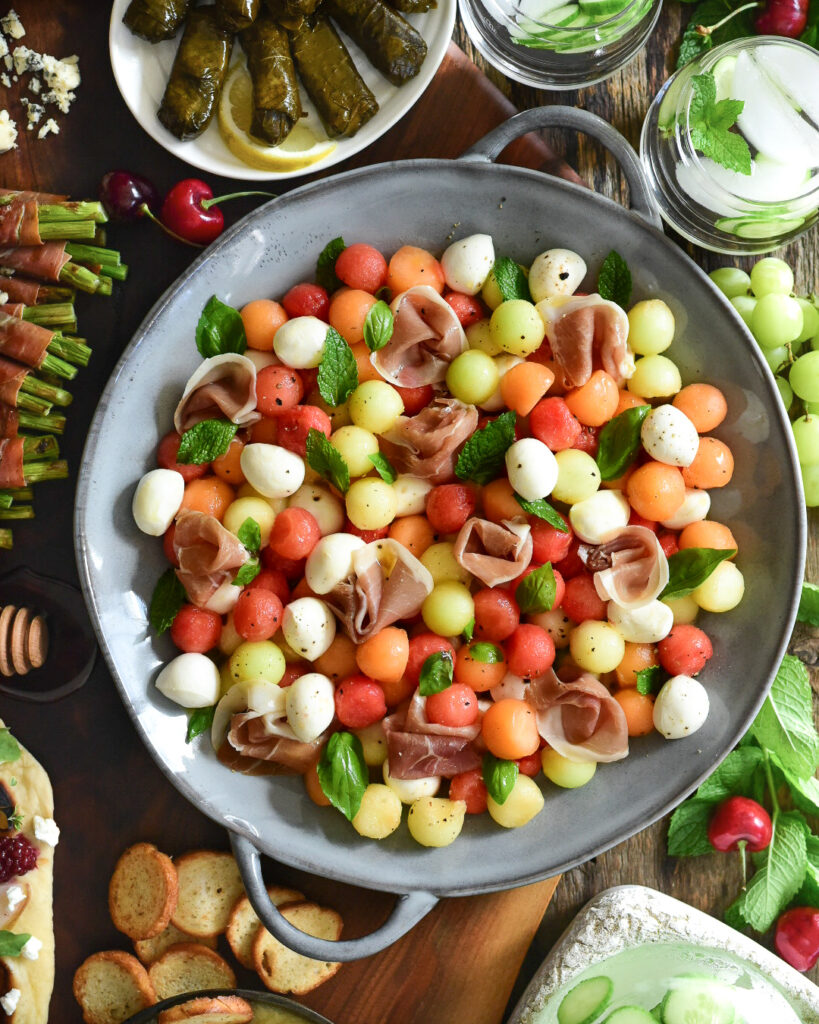 Proscuitto, melon, bocconcini salad with fresh herbs in a large double handle bowl.