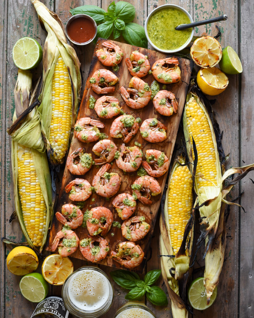 Cedar plank with shrimp. Corn, lemons, sauce, beer and basel surround the board.