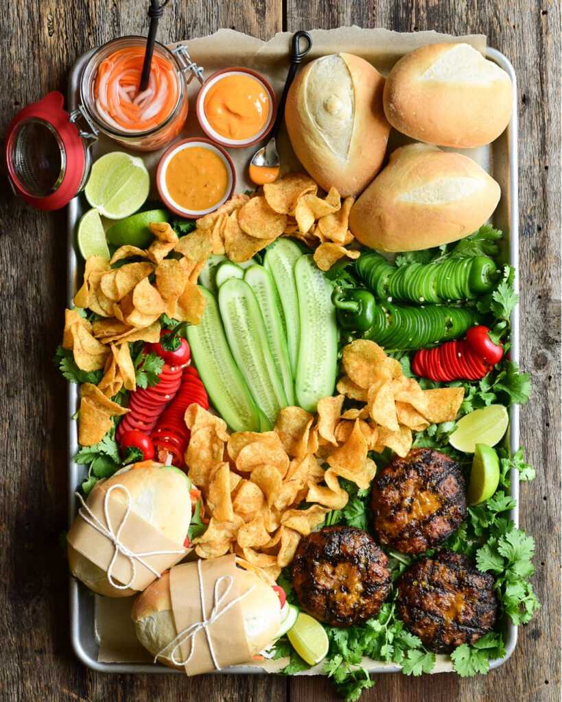 A large platter of buns, pork burger patties, fresh veggies, sauces and pickled carrots and daikons to make a Bahn Mi inspired burger.