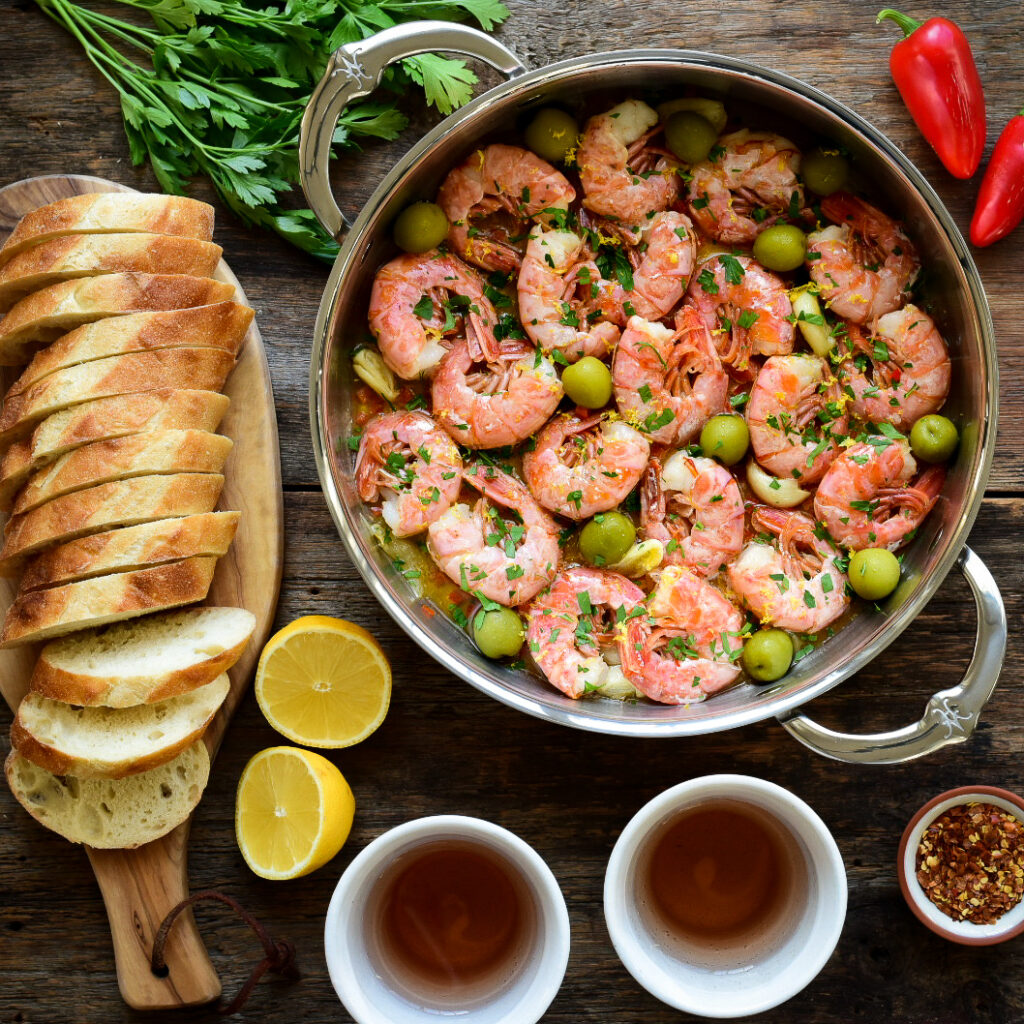 Top down image of pan with a garlic shrimp (Gambas al Ajillo). Surrounded by bread, wine, lemons and peppers.