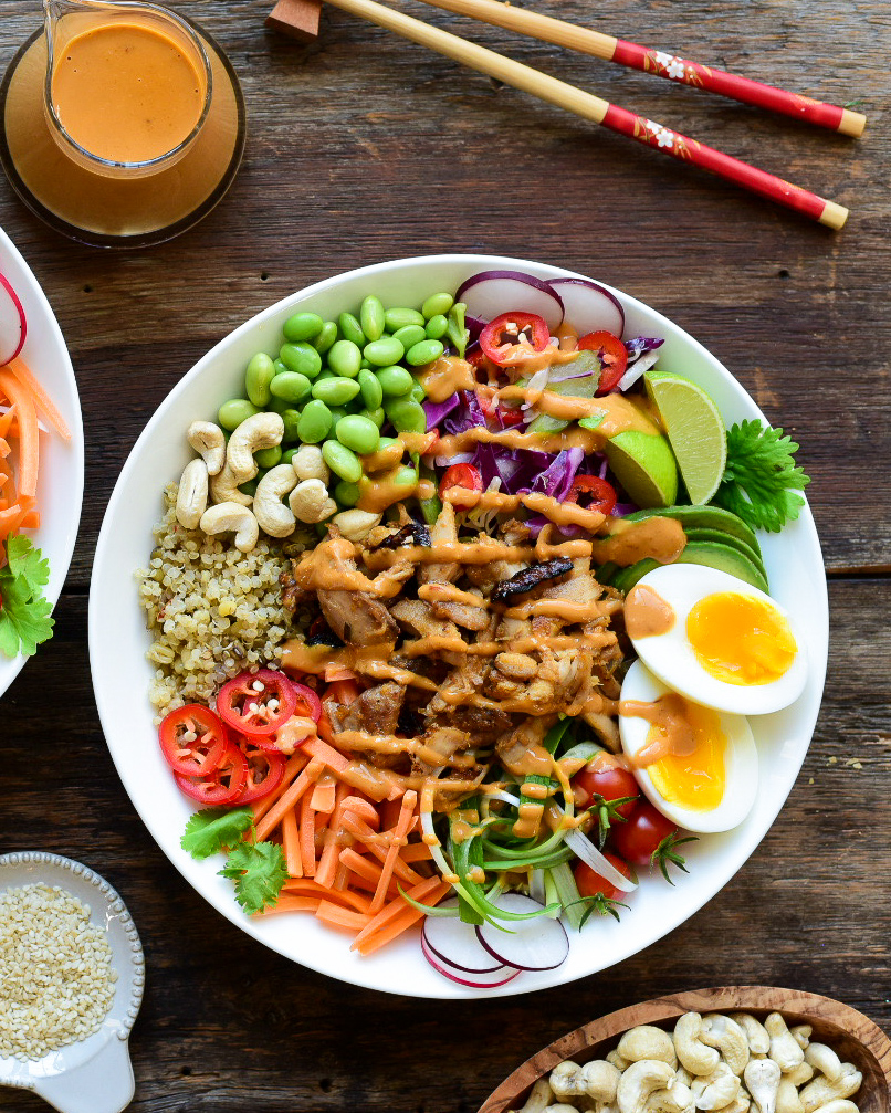 A colourful chicken grain bowl with peanut sauce, boiled eggs and veggies.