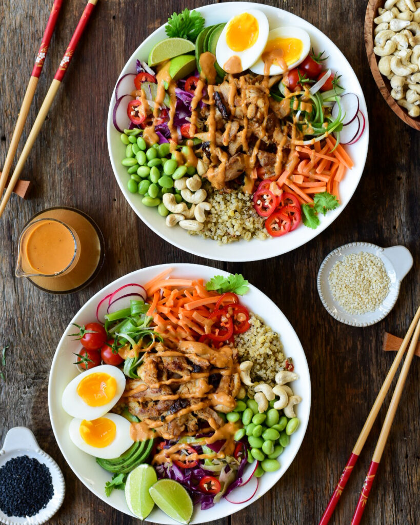 Two colourful chicken grain bowls with peanut sauce, boiled eggs and veggies.
