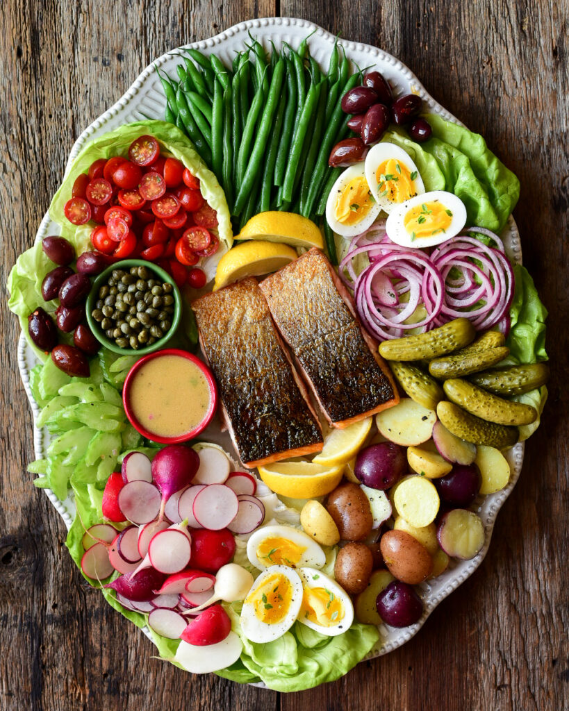 A large colourful platter of a salmon Niçoise-Style Salad.