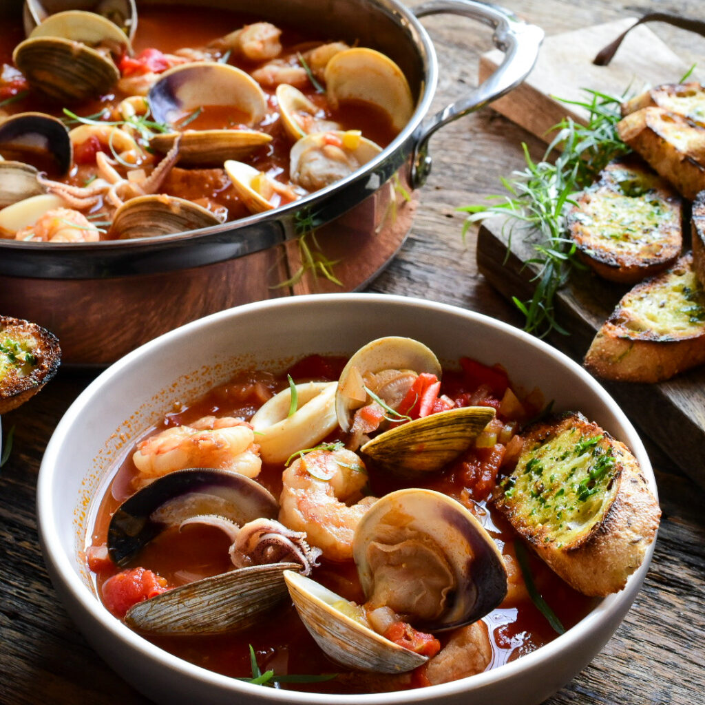 An images of a pot and soup bowl filled with Cioppino (Fisherman's Stew) with clams, shrimp and squid.  Garlic and herb toast in the background.