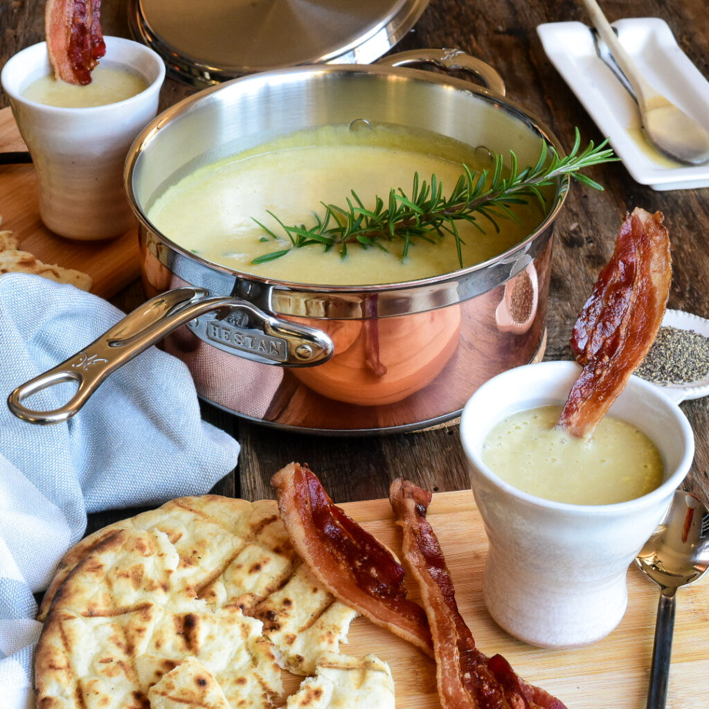 Leek and potato soup in a copper pot with a large