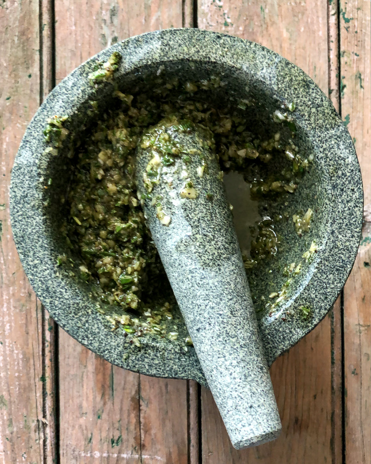 A top down image of a mortar & pestle with garlic, sea salt, herbs and olive oil.