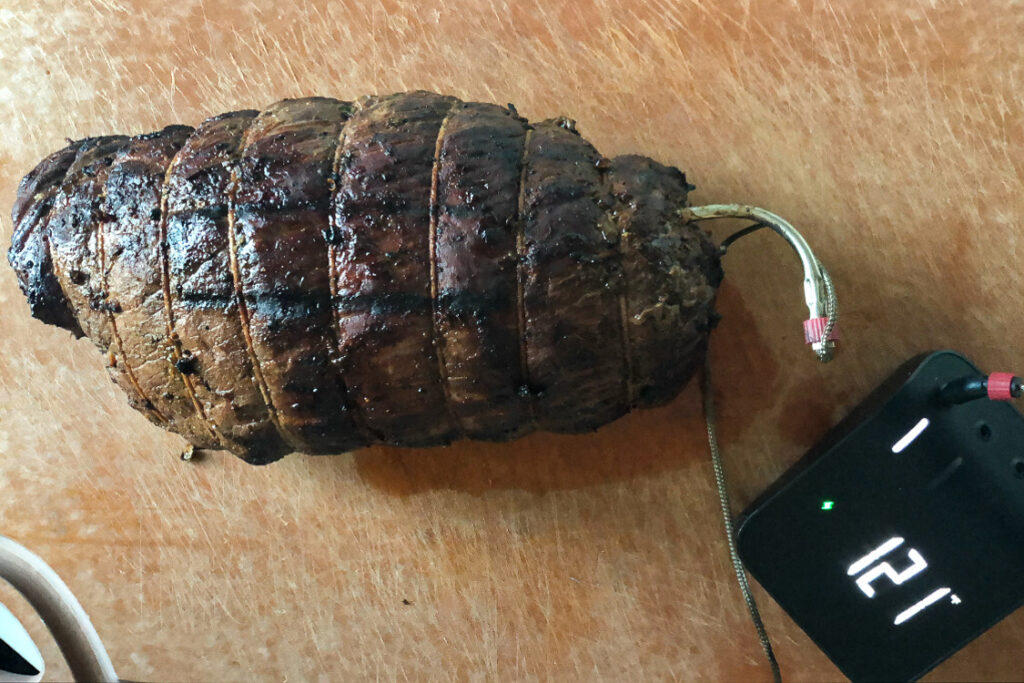 A rested image of grilled roast with a temperature probe reading 121 °F and ready to carve.
