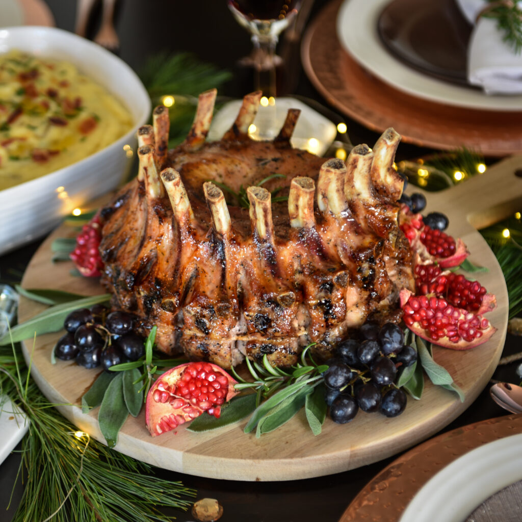 Plated crown roast of pork garneshes with herbs, grapes, and pomegranites on the dinner table. Table is set with dishes and wine glasses.